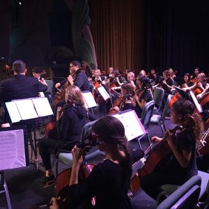 Cello students on stage behind professional cellists