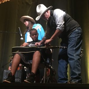 A musician in a cowboy hat showing a student how to play slide guitar.